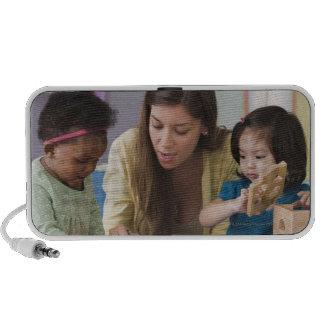 Helfende Kleinkindfarbe des Lehrers am Kindertages Laptop Lautsprecher