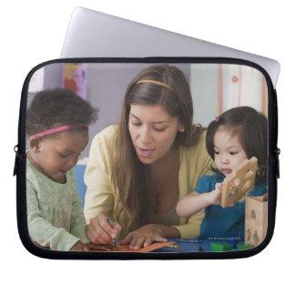 Helfende Kleinkindfarbe des Lehrers am Kindertages Laptop Sleeve Schutzhüllen