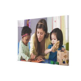 Helfende Kleinkindfarbe des Lehrers am Kindertages Leinwand Drucke