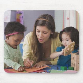Helfende Kleinkindfarbe des Lehrers am Kindertages Mousepads