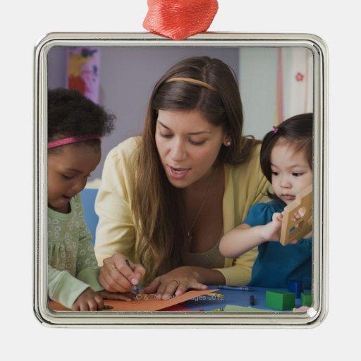 Helfende Kleinkindfarbe des Lehrers am Kindertages Weinachtsornamente