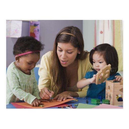 Helfende Kleinkindfarbe des Lehrers am Kindertages Postkarten
