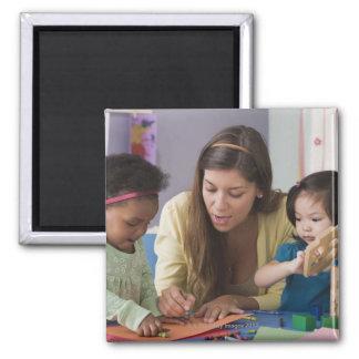 Helfende Kleinkindfarbe des Lehrers am Kindertages Quadratischer Magnet