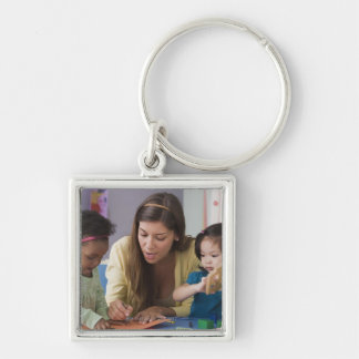 Helfende Kleinkindfarbe des Lehrers am Kindertages Silberfarbener Quadratischer Schlüsselanhänger