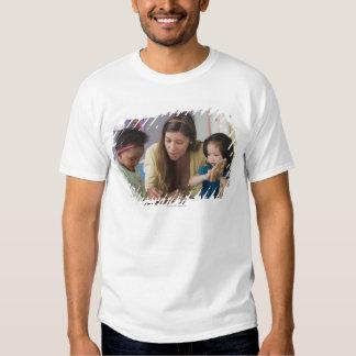 Helfende Kleinkindfarbe des Lehrers am Kindertages T Shirts