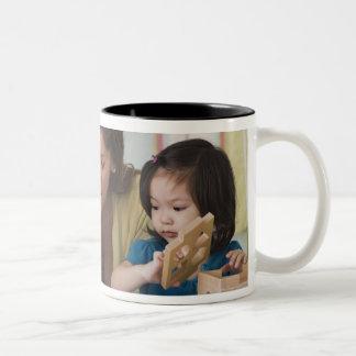 Helfende Kleinkindfarbe des Lehrers am Kindertages Zweifarbige Tasse