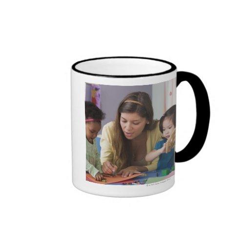 Helfende Kleinkindfarbe des Lehrers am Kindertages Teehaferl