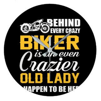 Hinter verrücktem Radfahrer ist verrücktere alte Große Wanduhr