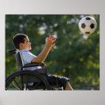 Hispanischer Junge, 8, im Rollstuhl mit Fußball Posterdrucke