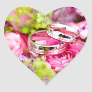 Hochzeitsringe und rosa Herz-Aufkleber