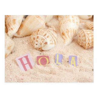 Hola, hallo auf spanisch auf einem sandigen Strand Postkarte