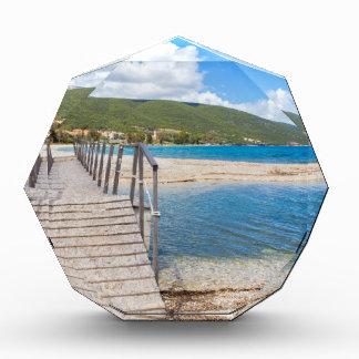 Hölzerne Fußgängerbrücke auf griechischem Strand Auszeichnung