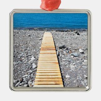 Hölzerner Fußweg auf dem Strand, der zu Silbernes Ornament