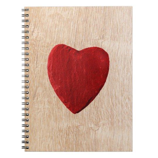 Holzhintergrund mit Herz Spiral Notizblock