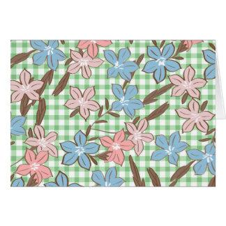 Hübsche blaue und rosa Blumen auf grünem kariertem Karte