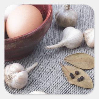 Huhneier und Knoblauch und Gewürze auf der Küche Quadratischer Aufkleber