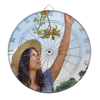 Junge Frau, die rote Äpfel vom Apfelbaum auswählt Dartscheibe