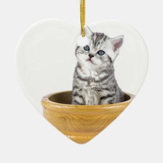 Junge silberne Tabbykatze, die in der hölzernen Keramik Herz-Ornament