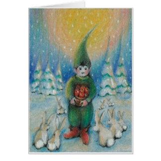 Junge tomte füttert Schneehäschen mit seinen Karte