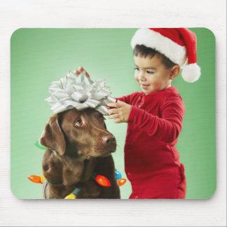 Junger Junge, der Weihnachtslichter um einen Hund Mousepad