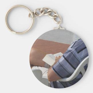 Junger Mann, der auf Stuhllesebuch sitzt Schlüsselanhänger