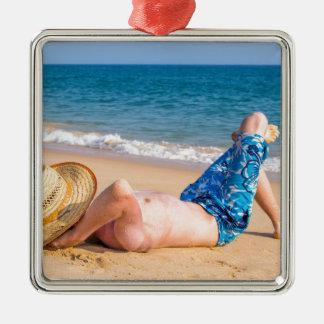 Junges touristisches Ein Sonnenbad nehmen auf Silbernes Ornament