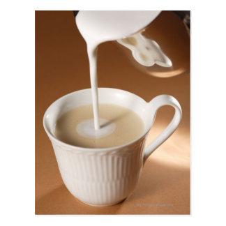 Kaffee mit der Milch, die herein ausgelaufen wird Postkarten