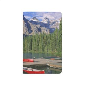 Kanada, Alberta, Moraine See. Rote Kanus erwarten Taschennotizbuch