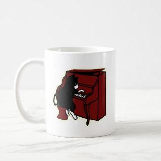Katze, die Klavier-Tasse spielt Kaffeetasse