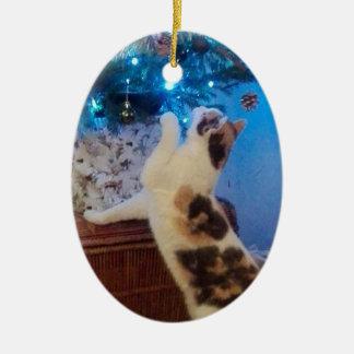 Katze, die mit Weihnachtsbaum spielt Ovales Keramik Ornament