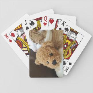 Katze hält alten Teddybären Spielkarten