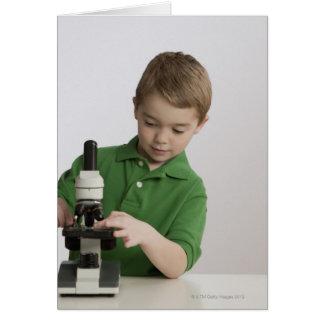 Kaukasischer Junge, der Mikroskop verwendet Karte