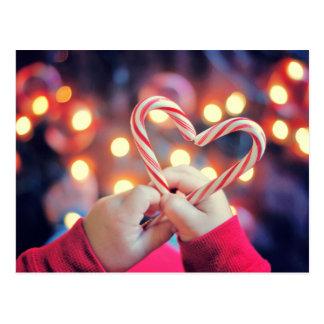 Kind, das Weihnachtssüßigkeit mit Herzform hält Postkarte