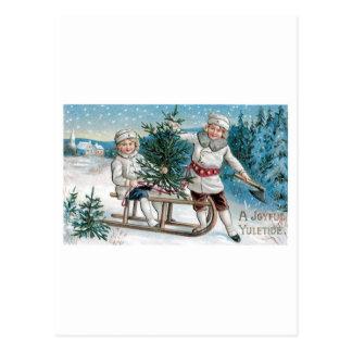 Kinder, die einen Weihnachtsbaum verringern Postkarte