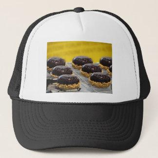 Kleine glasig-glänzende Schokoladenkuchen mit Truckerkappe