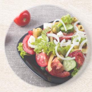 Kleine Schüssel Salat gemacht vom natürlichen Getränkeuntersetzer
