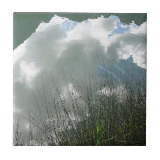 Kleiner Gebirgssee mit Reflexionen der Wolken Keramikfliese
