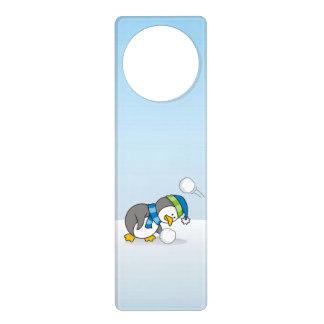 Kleiner Pinguin, der einen Schneeball erhält Türanhänger