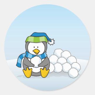 Kleiner Pinguin, der mit Schneebällen sitzt Runder Aufkleber