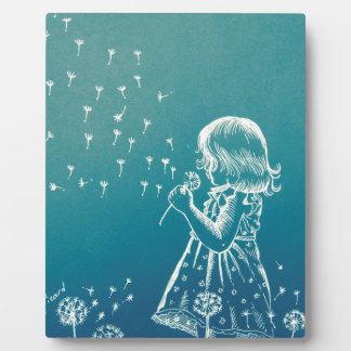 Kleines Mädchen, das auf einem Löwenzahn Fotoplatte
