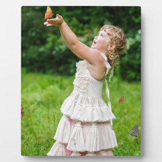 Kleines Mädchen, das ein Butterly fängt Fotoplatte