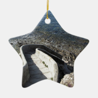 Konkretes Treppenhaus unten zum Meer. Gewundene Keramik Ornament
