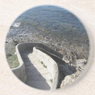 Konkretes Treppenhaus unten zum Meer. Gewundene Sandstein Untersetzer