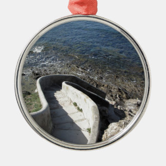 Konkretes Treppenhaus unten zum Meer. Gewundene Silbernes Ornament