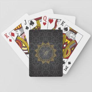 Kreis verziert Monogramm auf schwarzem Damast Spielkarten