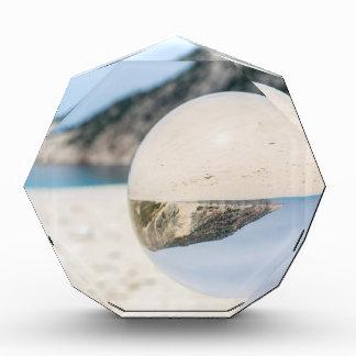 Kristallball auf sandigem griechischem Strand Auszeichnung