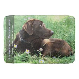Labrador-Retriever im Gras und in den lila Blumen Badematte