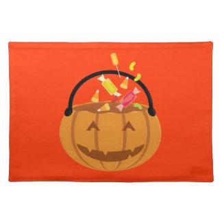 Lächelnder Halloween-Kürbis, der mit Süßigkeit Stofftischset