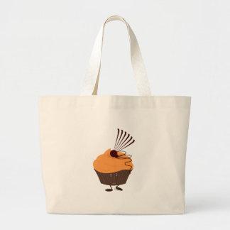 Lächelnder kleiner Kuchen mit orange Zuckergusse Einkaufstaschen
