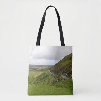 Landschaftsstraßenbiegungen um Hügel in Irland Tasche